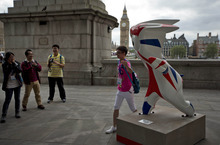 A man poses for a snapshot beside a statue of Mandeville, the Paralympic mascot, on the south bank of the River Thames as the