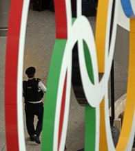 An airport police officer is framed by the Olympic Rings as he patrols an arrival terminal at Heathrow Airport, Tuesday, July 17, 2012 as London prepares for the 2012 Summer Olympics. (AP Photo/Charlie Riedel)