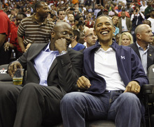 President Barack Obama, right, smiles as he talks with his former special assistant and personal aide Reggie Love, left, as they attend an Olympic men's exhibition basketball game with Brazil and Team USA in Washington, Monday, July 16, 2012. (AP Photo/Pablo Martinez Monsivais)