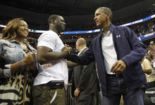 President Barack Obama, right, greet fans seated courtside as he arrives for an Olympic men's exhibition basketball game between Brazil and Team USA in Washington, Monday, July 16, 2012. (AP Photo/Pablo Martinez Monsivais)