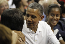 President Barack Obama, center, leans over to kiss first lady Michelle Obama, left, as their daughter Malia, right, watches while they attend the Olympic men's basketball exhibition game with Brazil and Team USA in Washington, Monday, July 16, 2012. (AP Photo/Pablo Martinez Monsivais)