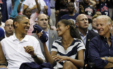 President Barack Obama, left, laughs with daughter Malia Obama after she caught a Nike T-shirt as they watch the Olympic men's exhibition basketball game between Team USA and Brazil, Monday, July 16, 2012, in Washington. She tossed the shirt to a child behind her. Team USA won 80-69. Seated at right is Vice President Joe Biden. (AP Photo/Alex Brandon)