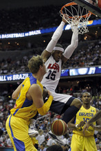 Team USA's Carmelo Anthony (15) dunks the ball in front of Brazil's Raul Togni Neto, left, and Leandro Mateus Barbosa during the first half of an Olympic men's exhibition basketball game, Monday, July 16, 2012, in Washington. Team USA won 80-69. (AP Photo/Alex Brandon)