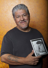 In this photo taken Monday, Sept. 12, 2011, writer and activist Luis J. Rodriguez holds a photo his late aunt Tia Chucha,  at his independent bookstore and community center named after her  in Los Angeles. His 1993 book