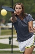 Leah Hogsten     The Salt Lake Tribune Laurel Schwendiman serves while playing pickleball. The popular game is played on a court with a lowered net with a perforated plastic baseball (similar to a whiffle ball) and wood or composite paddles. Salt Lake City has added pickleball courts to Reservoir Park due to the growing popularity of the sport.