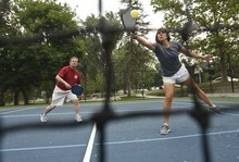 Leah Hogsten     The Salt Lake Tribune Laurel Schwendiman (right) returns a volley while playing with partner Rob Vrooman. Pickleball is played on a badminton court with a lowered net with a perforated plastic baseball (similar to a whiffle ball) and wood or composite paddles. Salt Lake City has added pickleball courts to Reservoir Park due to the growing popularity of the sport.