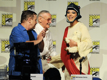 Actor Mark Hamill, left,  and Stan Lee, center, greet model Adrianne Curry at the start of the Stan Lee's World of Heroes panel on the first day of Comic-Con convention held at the San Diego Convention Center on Thursday July 12, 2012, in San Diego.  (Photo by Denis Poroy/Invision/AP)