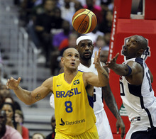 Team USA's Kobe Bryant, right, reaches for the ball from Brazil's Alex Ribeiro Garcia, with Team USA's LeBron James, watching during the first half of an Olympic men's exhibition basketball game, Monday, July 16, 2012, in Washington. Team USA won 80-69. (AP Photo/Alex Brandon)