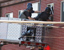 Police use a video camera to look inside an apartment  where the suspect in a shooting at a movie theatre lived in Aurora, Colo., Friday, July 20, 2012. As many as 12 people were killed and 50 injured at a shooting at the Century 16 movie theatre early Friday during the showing of the latest Batman movie. (AP Photo/Ed Andrieski)