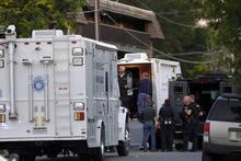 Police gather near an apartment house where the suspect in a shooting at a movie theatre lived in Aurora, Colo., Friday, July 20, 2012. As many as 14 people were killed and 50 injured at a shooting at the Century 16 movie theatre early Friday during the showing of the latest Batman movie. (AP Photo/Ed Andrieski)