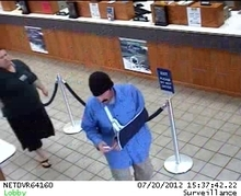 A suspected robber (blue shirt and sling) stands in line at the Utah First Credit Union in Midvale on July 20, 2012. Photo courtesy Unified Police Department.