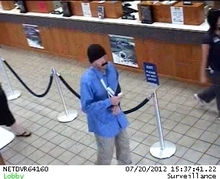 A suspected robber stands at the Utah First Credit Union in Midvale on July 20, 2012. Police say he handed the teller a note demanding money and saying he was armed. Photo courtesy Unified Police Department.