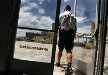 Scott Sommerdorf  |  The Salt Lake Tribune              A security guard walks out of The Gateway Megaplex, Friday, July 20, 2012. The message on the door has been there prior to the mass shooting in Colorado.