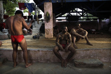 In this in Wednesday, July 18, 2012, photo, an Indian wrestler, left, exercises while others take a break after a training session at the Guru Hanuman Akhara or a wrestling school, in New Delhi India. India has hundreds of local academies for mud wrestling, which is an age old and a very popular sports of Indian villages. The academies also play a role to train wrestlers for the Olympics competed on synthetic mats. India, which has only nine individual medals to show for in the Olympics, has won two bronze medals through its wrestlers - K.D. Jadhav (Helsinki, 1952) and Sushil Kumar (Beijing, 2008). (AP Photo/Manish Swarup)