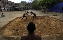 In this Thursday, July 12, 2012 photo, Indian wrestlers get ready for a bout during a practice session in mud pit at the Sports Authority of India complex, in Bhiwani, 122 kilometers (76 miles) from New Delhi, India. India has hundreds of local academies for mud wrestling, which is an age old and a very popular sports of Indian villages. The academies also play a role to train wrestlers for the Olympics competed on synthetic mats. India, which has only nine individual medals to show for in the Olympics, has won two bronze medals through its wrestlers - K.D. Jadhav (Helsinki, 1952) and Sushil Kumar (Beijing, 2008). (AP Photo/Manish Swarup)
