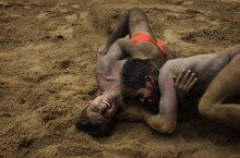 In this Thursday, July 12, 2012 photo, Indian wrestlers practice in a mud pit at the Sports Authority of India complex, in Bhiwani, 122 kilometers (76 miles) from New Delhi, India. India has hundreds of local academies for mud wrestling, which is an age old and a very popular sports of Indian villages. The academies also play a role to train wrestlers for the Olympic sport competed on synthetic mats. India, which has only nine individual medals to show for in the Olympics, has won two bronze medals through its wrestlers - K.D. Jadhav (Helsinki, 1952) and Sushil Kumar (Beijing, 2008). (AP Photo/Manish Swarup)