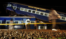 Indian people walk next to wrecked rail cars in Kasara, India, Friday, July 20, 2012. A fast moving express train collided with some derailed coaches of a commuter train that were lying on the tracks Thursday, according to Press Trust of India. (AP Photo/Rajanish Kakade)