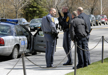 FILE - In this April 16, 2007, file photo, state and local police wait for a building to be cleared by police on the Virginia Tech campus in Blacksburg, Va., following a shooting incident. Gun control advocates sputter at their own impotence. The National Rifle Association is politically ascendant. And Barack Obama's White House pledges to safeguard the Second Amendment in its first official response to the deaths of at least 12 innocents in a mass shooting at a new Batman movie screening in suburban Denver. Once, every highly publicized outbreak of gun violence produced strong calls from Democrats and a few Republicans for tougher controls on firearms. Now those pleas are muted, a political paradox that's grown more pronounced in an era scarred by Columbine, Virginia Tech, the wounding of a congresswoman and now the shootings in a suburban movie theater where carnage is expected on-screen only. (AP Photo/Don Petersen)