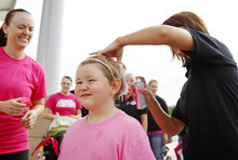 Natalie Buck, 5, of Waterloo, front, has her hair painted pink by Cami Franzen, right, of LaJames following the 5K Run/Walk/Ride/Stroll/Roll for two missing Iowa cousins, Lyric Cook-Morrissey, 10, and Elizabeth Collins, 8, in Waterloo, Iowa on Saturday, July 21, 2012. Investigators reclassified the disappearance of two missing Iowa cousins as an abduction case Friday after an FBI dive team failed to find their bodies in a lake near where they were last seen a week ago. (AP Photo/Waterloo Courier, Dawn J. Sagert)