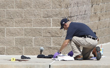 An investigator inspects evidence outside the Century 16 movie theater east of the Aurora Mall in Aurora, Colo. on Friday, July 20, 2012. A gunman in a gas mask barged into the crowded Denver-area theater during a midnight showing of the Batman movie on Friday, hurled a gas canister and then opened fire in one of the deadliest mass shootings in recent U.S. history. (AP Photo/David Zalubowski)