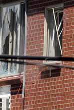 Debris and cords fall out of a window as a