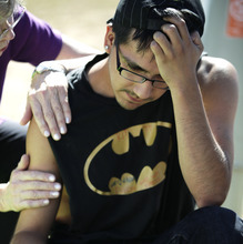Isaac Pacheo, who said he was a good friend of theater shooting victim Alex Sullivan, is comforted, Saturday, July 21, 2012, as he visits a memorial near the movie theater in Aurora, Colo.  Twelve people were killed and dozens were injured in the attack early Friday at the packed theater during a showing of the Batman movie,