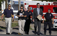 Sgt. Cassidy Carlson, second from left, spokesperson for the Aurora Police Department, crosses the street with others for a media availability near the apartment of alleged gunman James Holmes, Saturday, July 21, 2012, in Aurora, Colo. Authorities reported that 12 died and dozens more were shot during an assault at a movie theater midnight premiere of