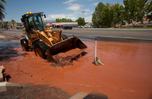 Utah Department of Transportation worker Jim Hosey uses a front end loader to remove mud and water from a clogged drainage ditch on Bluff Street Monday, July 16, 2012 in St. George after monsoonal rains flooded a number of area streets and homes Sunday leaving behind a muddy mess.