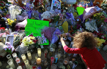Serenity Brydon, 7, places a rosary around a bear at a memorial near the the Century 16 movie theater Sunday, July 22, 2012, in Aurora, Colo. Twelve people were killed and dozens were injured in a shooting attack early Friday at the packed theater during a showing of the Batman movie,