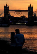London residents Rajan Malhotra, right, and Amy Dhillon watch as the sun sets behind the Tower Bridge with a display of Olympic rings in the distance Saturday, July 21, 2012, in London. The 2012 London Olympics open on Friday, July 27. (AP Photo/Charlie Riedel)