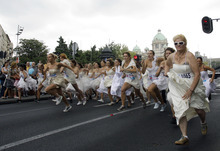 Brides participate in a race in central Belgrade, Serbia, Sunday, July 22, 2012. The winner and two runners-up of the Bridal Race, organized by a local magazine, receive numerous awards, including the wedding gown they had chosen to race in. (AP Photo/Darko Vojinovic)