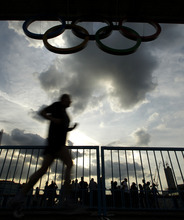 A jogger crosses the Tower Bridge below a display of Olympic rings Saturday, July 21, 2012, in London. The opening ceremonies for the 2012 London Olympic Games are scheduled for Friday, July 27. (AP Photo/Charlie Riedel)