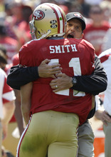San Francisco 49ers quarterback Alex Smith (11) is hugged by coach Jim Harbaugh after scoring on a 1-yard touchdown run against the Seattle Seahawks in the second quarter of an NFL football game in San Francisco, Sunday, Sept. 11, 2011. (AP Photo/Marcio Jose Sanchez)