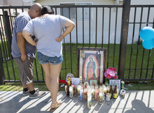 A couple who didn't want to be identified look at the memorial set up for Manuel Diaz, 25, who was killed in an officer-involved shooting in Anaheim, Calif., Sunday July 22, 2012.  The incident sparked a Saturday night melee and Sunday protests.  (AP Photo/The Orange County Register, Mindy Schauer)