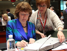 EU foreign policy chief Catherine Ashton, left, signs documents, prior to the start of an EU foreign affairs meeting at the European Council building in Brussels, Monday, July 23, 2012. The European Union foreign chief says the escalating bloodshed in Syria was sparking concerns that the conflict may spill over into neighboring countries. (AP Photo/Yves Logghe)