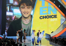 From right, Rupert Grint, Tom Felton and in background via satellite Daniel Radcliffe accept the