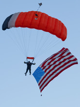 Michael Mangum  |  Special to the Tribune  A skydiver with an American flag approaches a landing in the West Jordan Arena at the beginning of Merrill Osmond's Youth Pioneer Pageant in West Jordan on Monday, July 23, 2012.