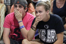 Andrew Hanselman, left, of Bucks County, Pa., and Maddy Pryor, a senior, from Neptune, N.J., react as they listen to a television in the HUB on the Penn State University main campus in State College, Pa., as the NCAA sanctions against the Penn State University football program are announced Monday, July 23, 2012.  (AP Photo/Gene J. Puskar)