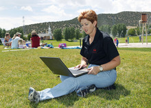 Al Hartmann  |  The Salt Lake Tribune Mayor Heather Jackson works on her laptop sitting in the grass in Nolan Park at Eagle Mountain.    The city is planning to be the first in Utah to get citywide wifi. The local internet provider DirectComm is outfitting the town with access towers so subscribers can get wifi access anywhere in Eagle Mountain.