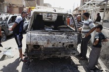 People inspect a destroyed vehicle after a bomb attack in Madain, about 15 miles southeast of Baghdad, Iraq, on Monday, July 23, 2012. An onslaught of bombings and shootings killed scores of people across Iraq on Monday, in the nation's deadliest day so far this year. The attacks come days after the leader of al-Qaida in Iraq declared a new offensive seeking to re-assert its might in the security vacuum left by the departing Americans. (AP Photo/Karim Kadim)