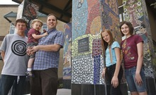 Leah Hogsten  |  The Salt Lake Tribune Over 60 students from North Davis Preparatory Academy including students, from left: Tyler Hammond, Lexie Bazzano, Andra Emmertson and mosaic artist Roger Whiting (holding son Wesley, 2) worked for 5 months to design a mosaic for the entrance columns to their school in Layton.