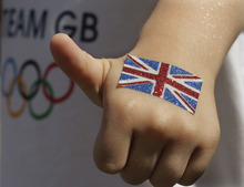 A boy gestures prior to the start of the women's group E soccer match between Great Britain and New Zealand, at the Millennium Stadium in Cardiff, Wales, at the 2012 London Summer Olympics, Wednesday, July 25, 2012. (AP Photo/Luca Bruno)
