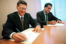 FILE - In this Sept. 25, 1998, photo released by Domin's Pizza, Thomas S. Monaghan, founder and chairman of Domino's Pizza, Inc., left, and Mitt Romney, managing director of Bain Capital, Inc., sign an agreement for Monaghan to sell a