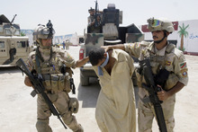 Iraqi army soldiers bring in a blindfolded and handcuffed suspected al-Qaida member to detention centers in an Iraqi army base in Baghdad, Iraq, Wednesday, June 16, 2010. Iraqi security forces raided some villages in Arab Jabour, south of Baghdad, and detained 16 men suspected members of al-Qaida. (AP Photo)
