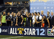 MLS All Stars' Dwayne De Rosario, center, of D.C. United, holds the trophy with teammates after defeating Chelsea FC 3-2 in soccer's MLS All-Star game, Wednesday, July 25, 2012, in Chester, Pa. (AP Photo/Michael Perez)