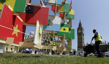 Workers put the finishing touches on the House of Flags display at Parliament Square in preparation for the 2012 Summer Olympics, Thursday, July 26, 2012, in London. More than 200 panels represent the countries participating in the London Games. (AP Photo/Eric Gay)