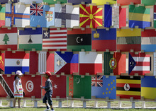 Children look stand near the House of Flags display at Parliament Square set up for the 2012 Summer Olympics, Thursday, July 26, 2012, in London. More than 200 panels represent the countries participating in the London Games. (AP Photo/Eric Gay)