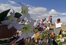 A woman holds flowers before placing them at the memorial across from the movie theater, Wednesday, July 25, 2012 in Aurora, Colo. Twelve people were killed and over 50 wounded in a shooting attack early Friday at the packed theater during a showing of the Batman movie,