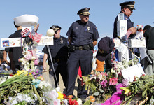 Aurora Police Chief Daniel Oates, center, looks at the memorial across from the movie theater, Wednesday, July 25, 2012 in Aurora, Colo. Twelve people were killed and over 50 wounded in a shooting attack early Friday at the packed theater during a showing of the Batman movie,
