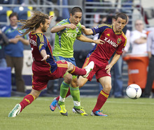 Real Salt Lake's Kyle Beckerman, left, and teammate Tony Beltran, right steal the ball away from Sounders' David Estrada during the first half of play in a MLS soccer match, Saturday, May 12, 2012, in Seattle. (AP PHOTO/Stephen Brashear)